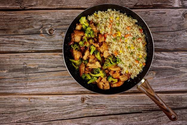 Faire sauter le poulet et le brocoli avec du riz dans une poêle sur une surface en bois