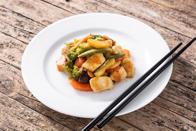 Faire sauter le poulet avec des légumes sur une table en bois rustique