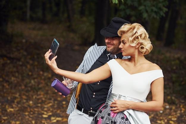 Faire un selfie. beau couple en vêtements à l'ancienne près de voiture rétro avec forêt en arrière-plan.