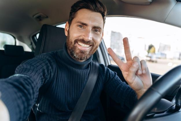 Faire un selfie. bel homme barbu tenant une caméra et faisant des gestes assis dans la voiture au siège du conducteur et prenant un autoportrait avec plaisir sourire