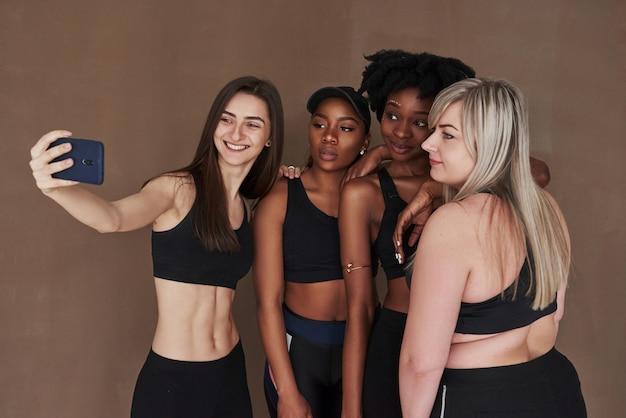Faire un selfie. groupe de femmes multiethniques debout contre l'espace brun