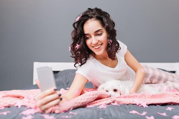 Faire selfie avec petit chien doux sur le lit entourent des guirlandes roses de jolie jeune femme brune en pyjama. bonne matinée à la maison, souriant, exprimant de vraies émotions positives