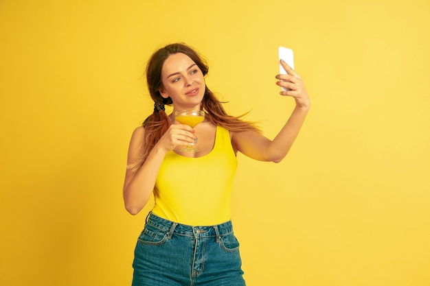 Faire selfie, vlog, sourire. portrait de femme caucasienne sur fond de studio jaune. beau modèle féminin. concept d'émotions humaines, expression faciale, ventes, publicité. l'été, les voyages, la station balnéaire.