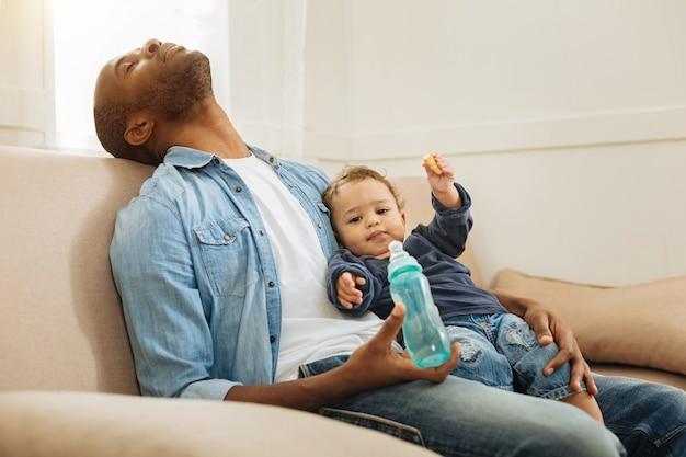 Faire une sieste. homme afro-américain fatigué aux cheveux noirs dormant et tenant son petit-fils et sa bouteille et assis sur le canapé