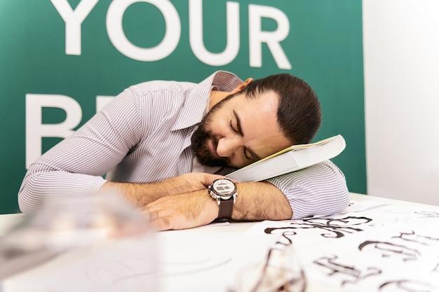 Faire la sieste. homme barbu aux cheveux noirs portant un t-shirt blanc sieste dans la salle de classe