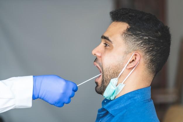 Faire un test de coronavirus à un jeune homme de la salive.
