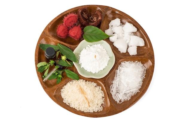 Faire tremper les cheveux avec de la fausse marguerite, du bixa orellana, du riz au jasmin, du menthol, du camphre et du bornéol isolé sur fond blanc.vue de dessus, pose à plat.
