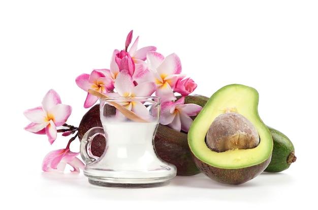 Faire tremper les cheveux avec de l'huile de noix de coco et des fruits d'avocat isolés sur fond blanc.