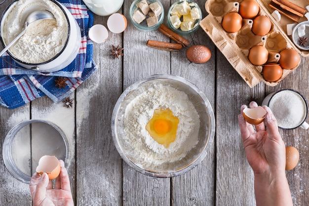Faire la vue de dessus de la pâte. les frais généraux des mains du boulanger casser l'oeuf sur la farine. ingrédients de cuisson pour pâtisserie sur bois rustique, cours de cuisine ou concept de recette.