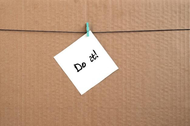 Fais le! la note est écrite sur un autocollant blanc qui pend avec une pince à linge sur une corde