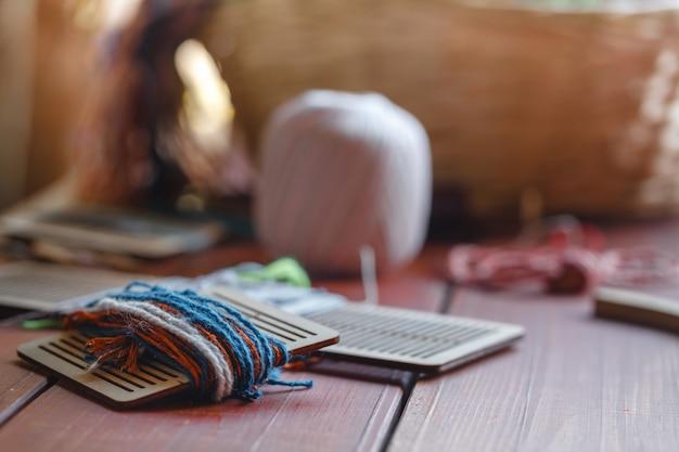 Faisceau de fil tissé zoom tourné contre la lumière montrant ses fils et fils sur le métier à tapis