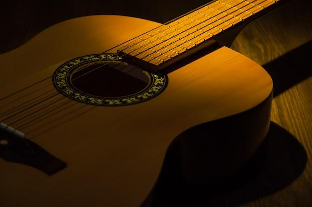 Un faisceau de lumière illumine une guitare acoustique sur une table en bois.