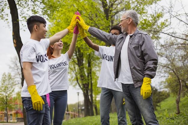 Faisons le. volontaires gais positifs debout et échangeant un high five