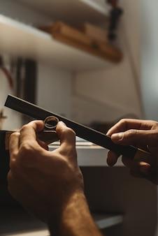 Fait avec amour. photo verticale des mains d'un bijoutier travaillant et façonnant une bague inachevée avec un outil à l'établi en atelier