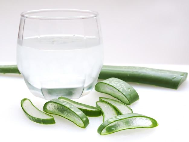 Fait maison avec du jus d'aloe vera, une boisson estivale rafraîchissante sur une table blanche.