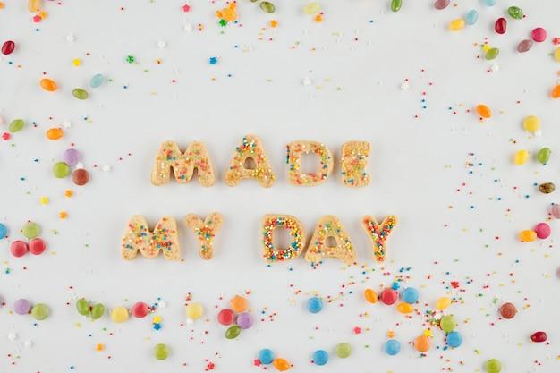 Fait mes mots de jour faits de biscuits au sucre savoureux sucrés et de délicieux bonbons colorés autour