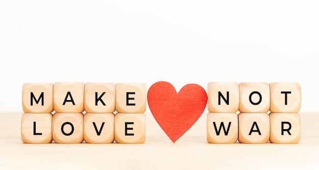 Faites l'amour pas la guerre citation. blocs en bois avec texte et coeur sur table.