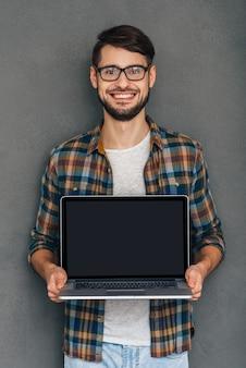 Faites attention à cela ! jeune homme confiant montrant son ordinateur portable et regardant la caméra avec le sourire en se tenant debout sur fond gris