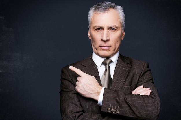 Faites attention à cela. portrait d'un homme âgé confiant en tenue de soirée regardant la caméra et pointant du doigt tout en se tenant contre le tableau noir