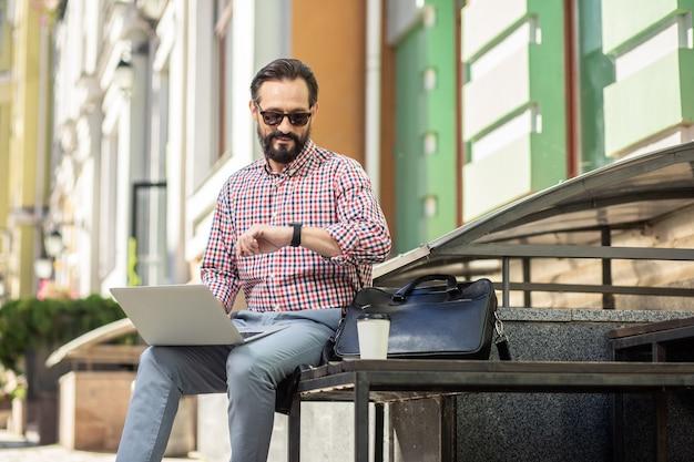 Faites attention à votre temps. homme adulte gai à l'aide de son ordinateur portable alors qu'il était assis dans la chaîne stéréo