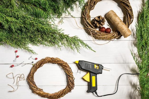 Faites une couronne de noël avec vos propres mains couronne de noël branche d'épinette et cadeaux sur un bois blanc...