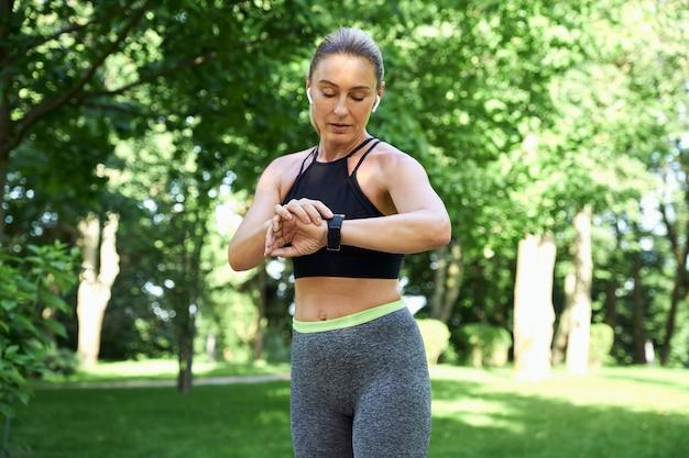 Faites du jogging le matin belle femme sportive en vêtements de sport et écouteurs en regardant sa montre et