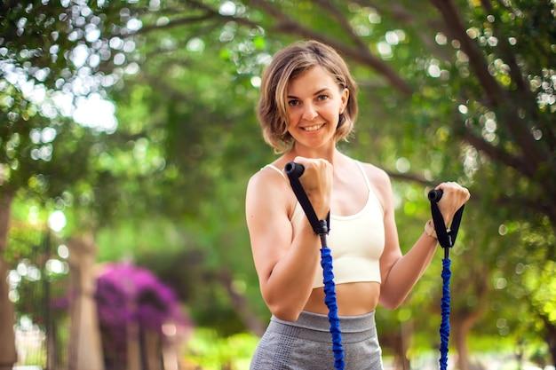 Faites de l'exercice avec des élastiques de fitness en plein air. femme s'entraînant en plein air. concept de remise en forme et de soins de santé