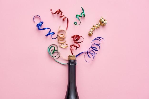 Faites la fête avec une bouteille de champagne avec des rubans brillants sur fond rose