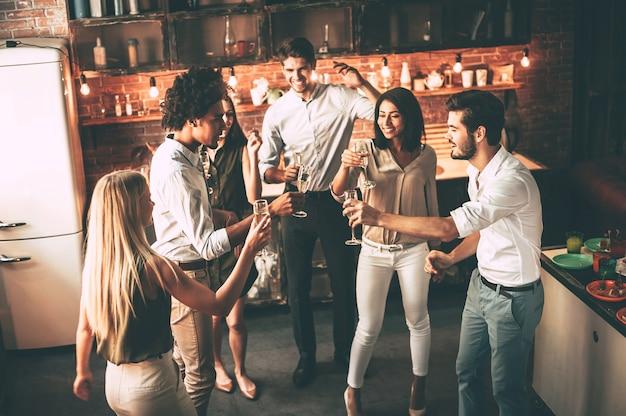 Faites la fête avec les meilleurs amis. vue de dessus de jeunes joyeux dansant et buvant tout en profitant d'une fête à la maison dans la cuisine