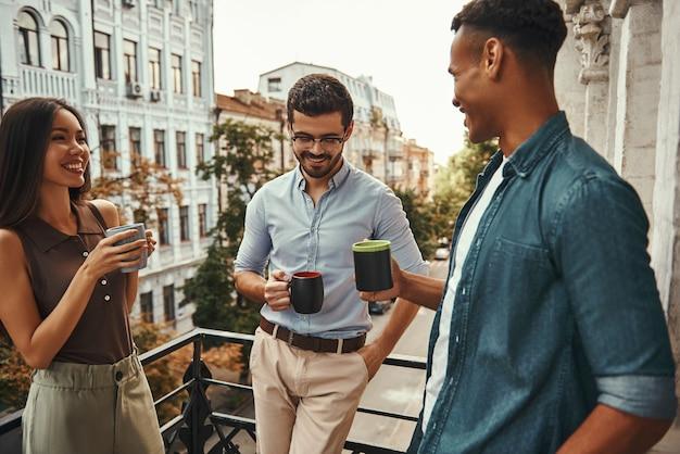 Faites une pause au travail de jeunes collègues positifs en tenue décontractée tenant des tasses et discutant de quelque chose avec
