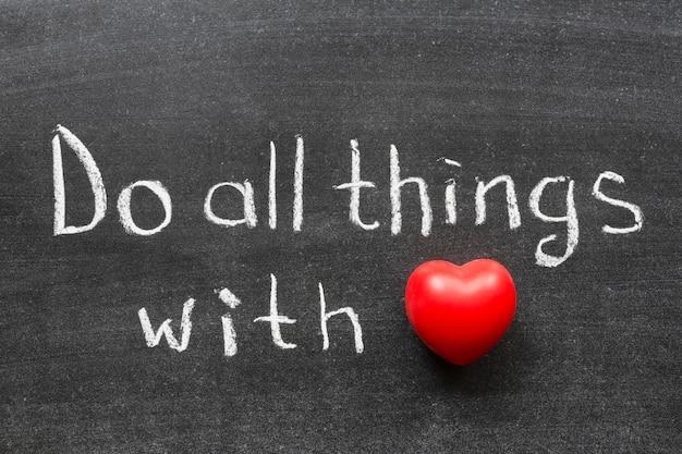 Faites toutes choses avec la phrase d'amour manuscrite sur le tableau noir de l'école