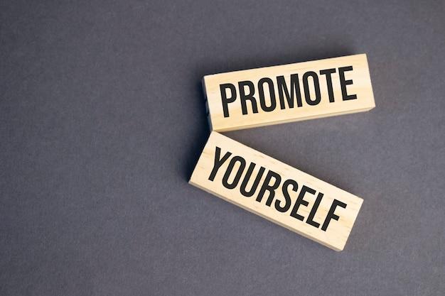 Faites vous promouvoir des mots sur des blocs de bois sur fond jaune. concept d'éthique des affaires.