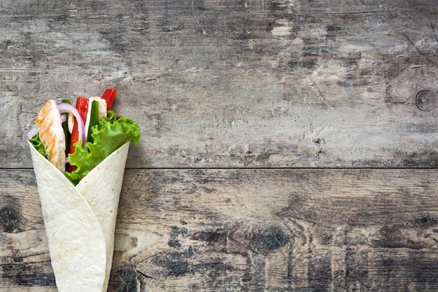 Fajita au poulet mexicain avec poivrons laitue et oignon sur une table en bois rustique