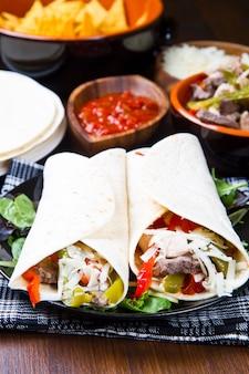 Fajitas au poulet et au bœuf avec légumes et tortillas