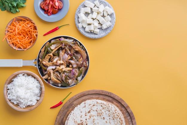 Fajitas et ingrédients vue de dessus et fond jaune