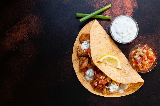 Fajitas mexicaines traditionnelles avec poulet et légumes, servies en tortilla avec sauce blanche et rouge, citron et oignons verts frais. vue de dessus. fond sombre. espace copie