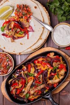 Fajitas de porc aux oignons et poivrons colorés, servis avec tortillas, salsa et crème sure.