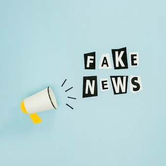 Fake news et mégaphone sur fond bleu