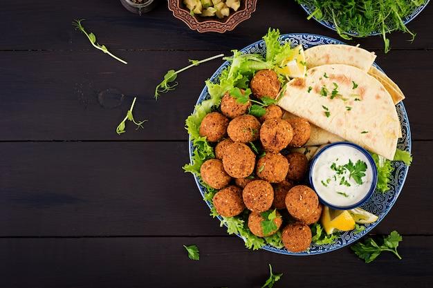 Falafel, houmous et pita. plats du moyen-orient ou arabes sur une table sombre
