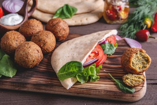 Falafel, légumes frais, sauce et pain pita sur table en bois