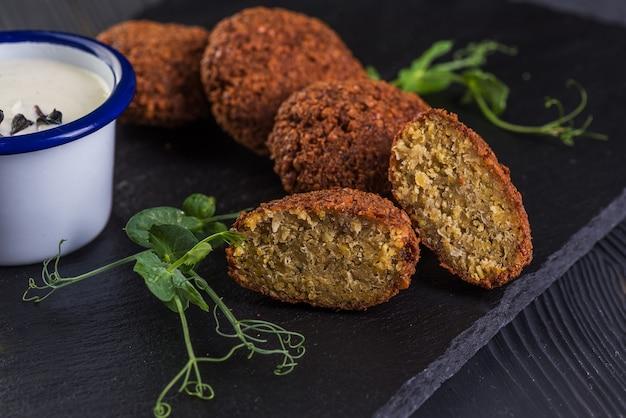 Falafel avec sauce à l'ail sur un plateau en pierre noire. nourriture végétalienne