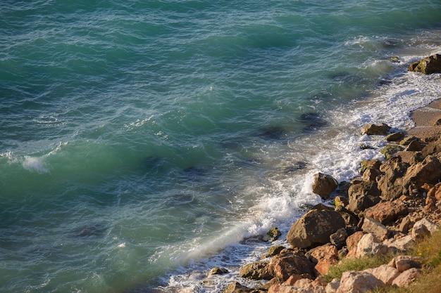 Falaise rocheuse et vagues turquoises paresseuses. calme, détente, concept de vacances. thème abstrait de la nature