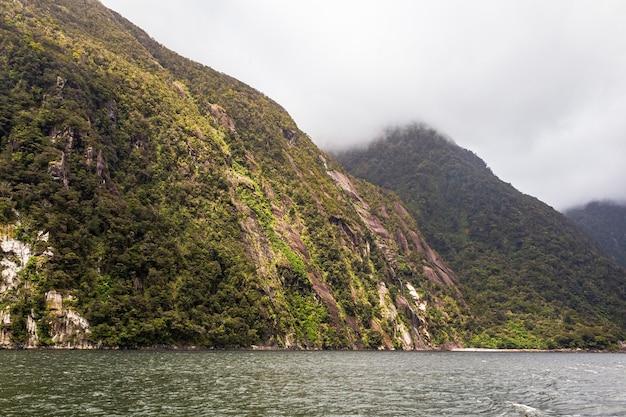 Falaises abruptes parmi la mer parc national de fiordland nouvelle-zélande