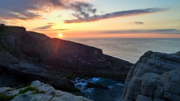 Falaises entourées par la mer sous la lumière du soleil pendant le coucher du soleil