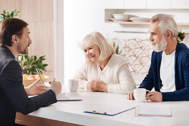 Familiarisation avec nos services. charmant agent immobilier professionnel confiant ayant une conversation avec les clients et utilisant un ordinateur portable tout en exprimant sa positivité