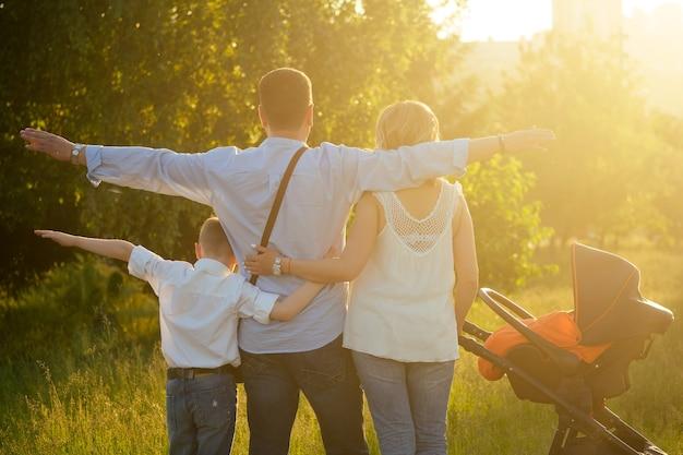 Famille de 4 personnes debout le dos au coucher du soleil.