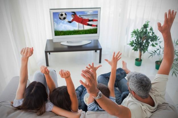 Famille acclamant et regardant la coupe du monde à la maison