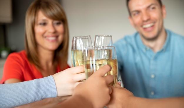 Famille acclamant avec des verres de champagne à la maison