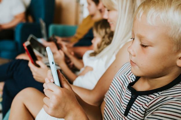 Famille accro au téléphone utilisant leurs téléphones sur le canapé