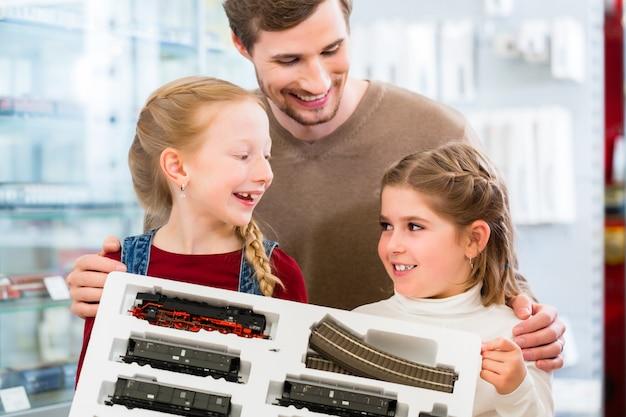 Famille achetant un chemin de fer modèle dans un magasin de jouets